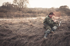 Hunter preparing for hunting in morinig field nearby river Royalty Free Stock Image