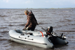 Hunter pulling motor boat. The hunter with motor rubber boat Royalty Free Stock Image