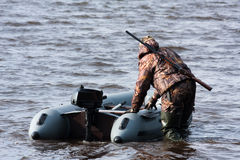 Hunter pulls the boat from shallow water. Hunter pulls the boat from shoal Stock Photo
