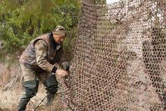Hunter pulls camouflage netting Royalty Free Stock Image