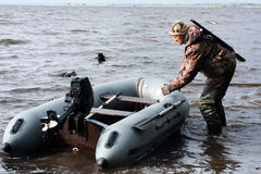 The hunter pulls motor boat. The hunter with motor rubber boat Stock Photography