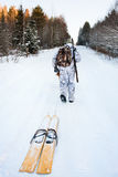 The hunter pulls the skis on the road Royalty Free Stock Photography