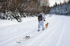 The hunter pulls the skis on winter road Royalty Free Stock Photo