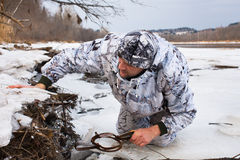 Hunter putting a leghold trap for beaver Royalty Free Stock Image