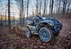 Hunter on quad bike. Young hunter on a quad bike searching for game in the forest Stock Photos