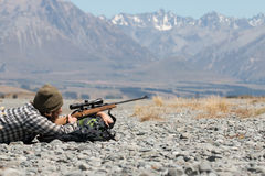 Hunter with riffle on background of mountains Royalty Free Stock Images