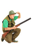 Hunter with rifle crouching and looking in the distance Stock Photo