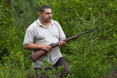 The hunter with rifle in a forest Stock Image