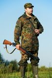 Hunter with rifle gun. Male hunter in camouflage clothes ready to hunt at lake bank with hunting rifle Royalty Free Stock Images