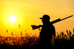 Hunter. Rifle Hunter Silhouetted in Beautiful Sunset. Summer Royalty Free Stock Images