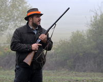 Hunter with rifle waiting for pheasant. Hunter with shotgun waiting for pheasant Stock Images