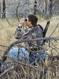 Hunter scouting with binoculars. A camouflaged hunter, sitting on a log, using his binoculars to search for nearby deer on opening day for hunting Stock Photos