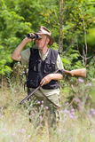 Hunter. Senior hunter with shotgun looking through binoculars in forest Stock Photos