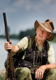 Hunter. Senior hunter with shotgun sitting beside lake Royalty Free Stock Photography