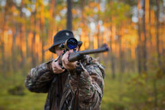 Hunter shooting a hunting gun. In woods Royalty Free Stock Images