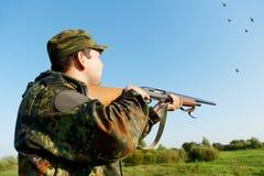 Hunter shooting with rifle gun stock photo