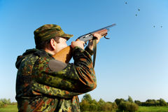 Hunter shooting with rifle gun Stock Photography