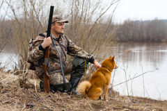 The hunter on the shore. The hunter with a gun and a dog sits on the shore Stock Photo