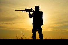 Hunter With Shotgun dans le coucher du soleil Photos stock