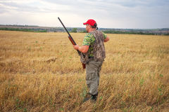 Hunter with shotgun on the field Royalty Free Stock Image