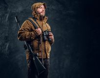 Hunter with shotgun holding binoculars and looking sideways. Studio photo against dark wall background royalty free stock images