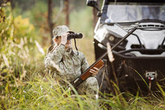 Hunter with shotgun looking through binoculars in forest royalty free stock photography