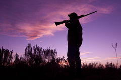 Hunter With Shotgun in Sunset. A hunter silhoutted against a dramatic sunset with shotgun royalty free stock image