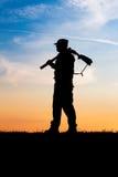 Hunter with shotgun in sunset Stock Photo