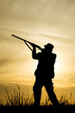 Hunter With Shotgun in Sunset. Hunter With Shotgun on the field in Sunset Stock Photo