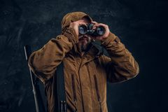 Hunter with shotgun watching through binoculars. Studio photo against dark wall background royalty free stock images