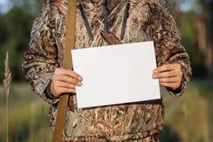 Hunter Showing Paper On Clipboard tegen stock afbeelding