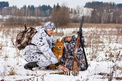 Hunter shows his son traces of animals on the snowy field Royalty Free Stock Photos