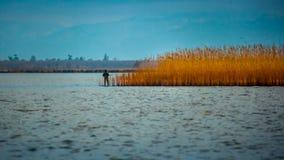 Hunter silhouette at sunrise, while hunting on the lake Paliasto Royalty Free Stock Image