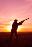Hunter Silhouetted at Sunset. An upland game hunter with shotgun silhouetted against a sunset Royalty Free Stock Image