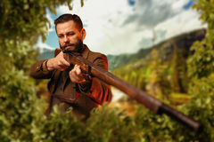 Hunter sitting in the bushes and aiming a rifle. Hunter man in vintage hunting clothing sitting in the bushes and aiming a rifle. Hunt lifestyle, antique weapon royalty free stock photos