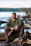 Hunter sitting  on the river. The hunter with gun at the river Stock Photography