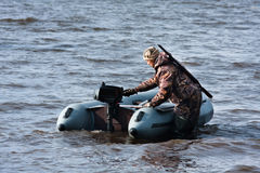 The hunter starts motor on the boat. The hunter with motor rubber boat Royalty Free Stock Photo
