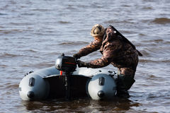 The hunter starts the motor of the boat. The hunter with motor rubber boat Royalty Free Stock Photos