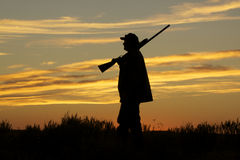 Hunter in Sunset. A hunter silhoutted against a dramatic sunset with shotgun Royalty Free Stock Photography