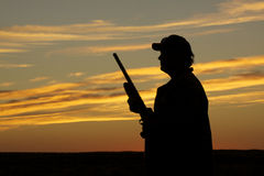 Hunter in Sunset. A hunter silhoutted against a dramatic sunset with shotgun at ready Royalty Free Stock Image
