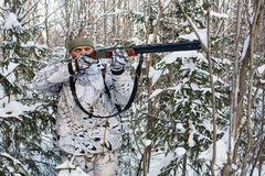 Hunter takes aim from a gun in the snowy forest Royalty Free Stock Photo