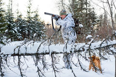 Hunter takes aim from a gun in the winter forest Stock Images