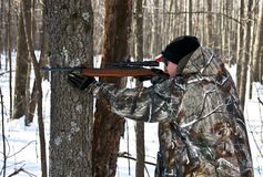 Hunter takes aim in the woods Stock Image