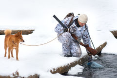 Hunter takes water from the river on a winter hunt stock photo