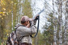 Hunter taking aim in the wildfowl. In the autumn forest Stock Photos
