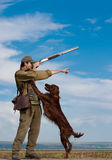 Hunter training his dog during a hunting party. Young hunter training his dog to go for the hunt during a hunting party Royalty Free Stock Photo