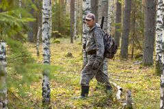 Hunter walking through the forest. Hunter in camouflage walking through the forest Royalty Free Stock Photography