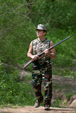 Hunter walking with rifle Stock Images