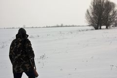 Hunter walking on the snowy field in winter stock photo