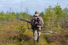 Hunter walking on the swamp. Hunter walking with gun on the swamp Stock Photo